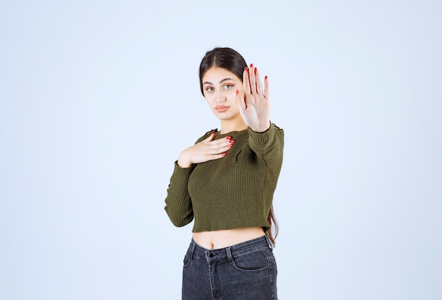 Un modello di giovane donna in piedi e facendo il segnale di stop.
