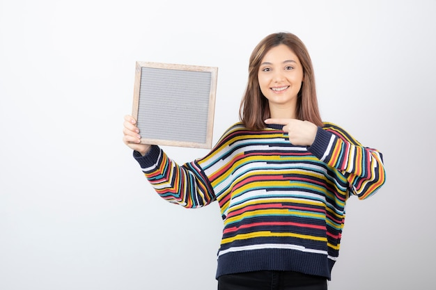 Modello di giovane donna in piedi e indicando una cornice.