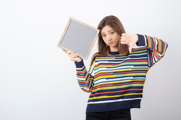 Young woman model standing and pointing at a frame. Free Photo