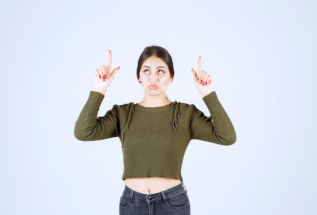 Modello di giovane donna in piedi e rivolto verso l'alto con l'indice.