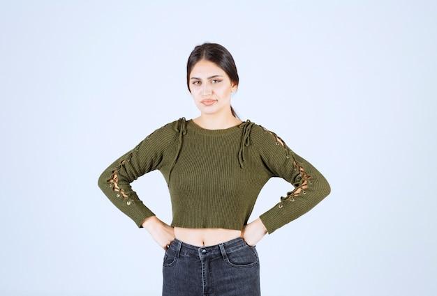 Modello di giovane donna in piedi con le mani sui fianchi e guardando lontano.