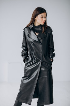 Young woman model wearing long black leather coat