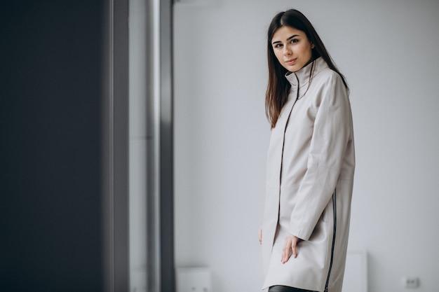 Young woman model wearing long gray coat