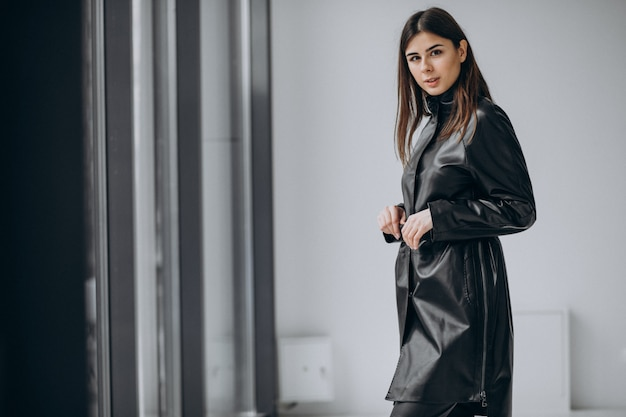Young woman model wearing long leather coat