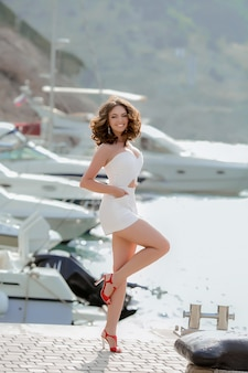 A young woman model in a white short dress walks in a bay near the sea with yachts.