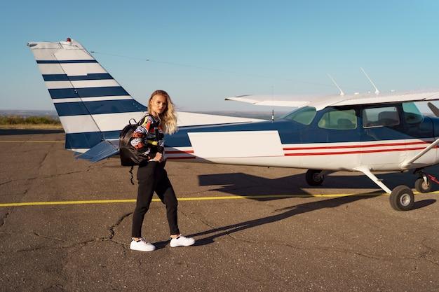 トレンディなカジュアルな服装と黒のバックパックを身に着けているプライベート飛行機の近くでポーズをとるモダンなヘアカットの若い女性モデル