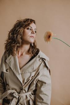 베이지색 트렌치 코트에 곱슬머리를 한 젊은 여성 모델이 거베라 꽃을 바라보고 있다