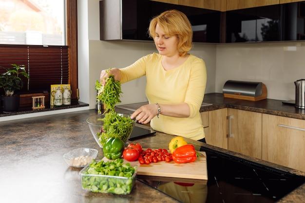 젊은 여자, 엄마와 아내가 부엌에서 그녀의 가족을 위해 신선한 야채 샐러드를 준비. 건강하고 적절한 영양의 개념. 비건 음식