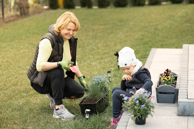 若い女性、お母さんは彼女の家の前または裏庭で彼女の女の赤ちゃんと一緒に花を植えることに従事しています。趣味、ガーデニングのコンセプト