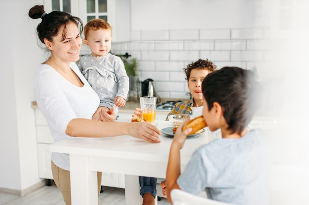 自宅の明るいキッチンで朝食を調理の手に女の赤ちゃんを持つ若い女性ママ、大きな幸せな家族