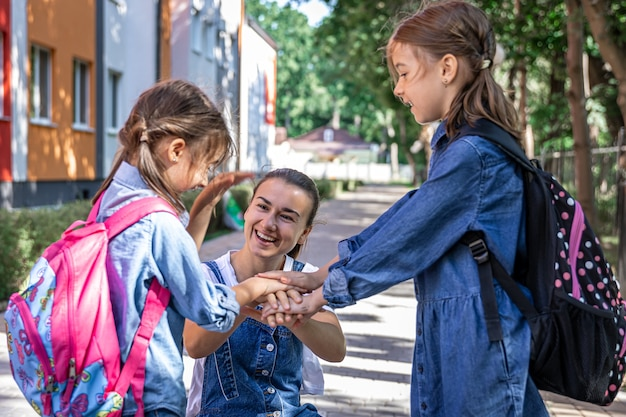 A young woman morally supports the daughters holding hands encourages the children, accompanies students to school.