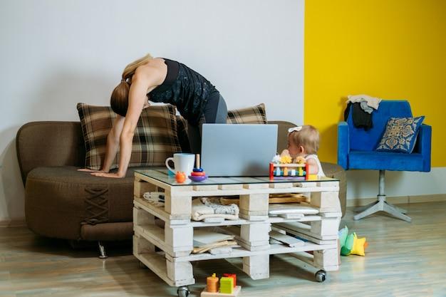 若い女性の母親は、自宅で赤ちゃんの幼児の娘と一緒にソファに座ってヨガの練習を見ています