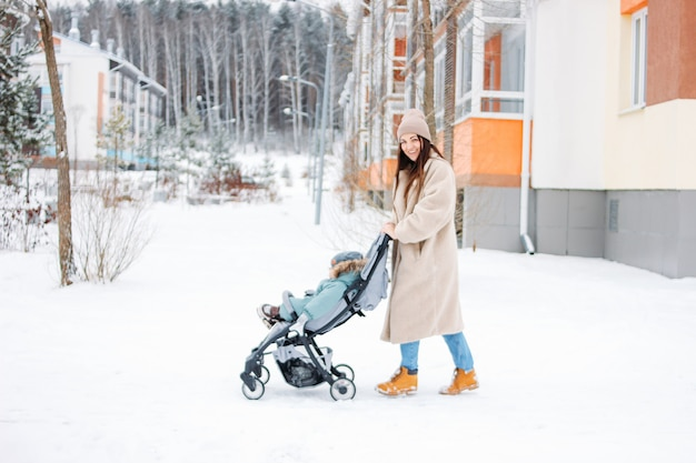 Young woman mother with child baby boy in stroller walking on winter street