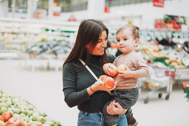 Young woman mother with cute baby boy toddler child on hands buys the fresh apples in supermarket