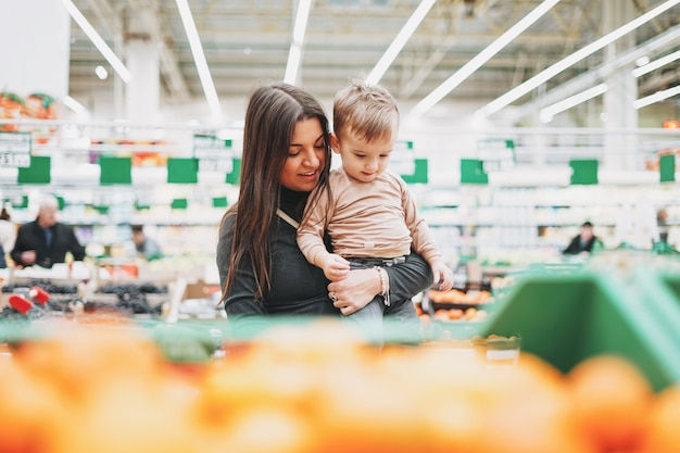 Young woman mother with cute baby boy toddler child on hands buys the fresh fruits in supermarket