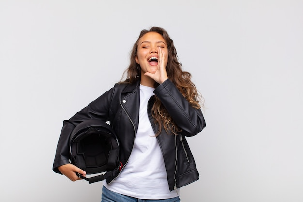 Young woman motorbike rider feeling happy, excited and positive, giving a big shout out with hands next to mouth, calling out