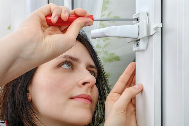 Young woman mounts window limiter on frame, she tightens bolt using  screwdriver.