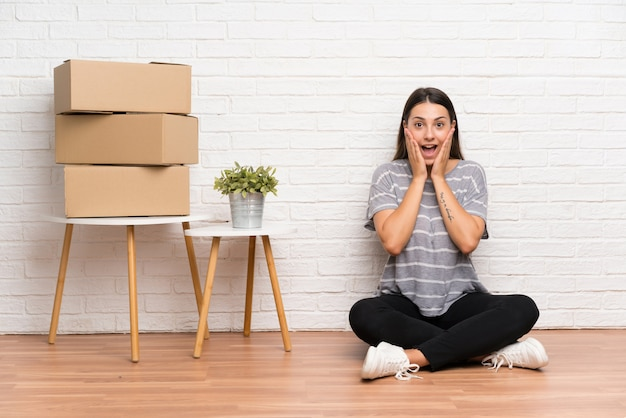 Молодая женщина переезжает в новый дом среди коробок с удивленным выражением лица