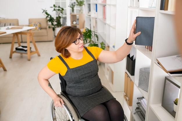 Молодая женщина, перемещающаяся в инвалидной коляске, кладет книгу на полку во время уборки гостиной