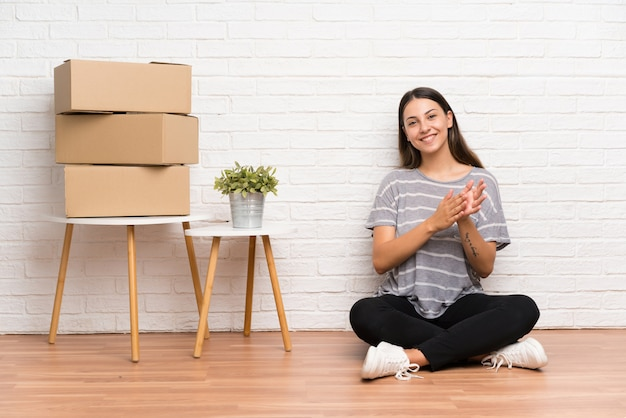Young woman moving in new home among boxes applauding