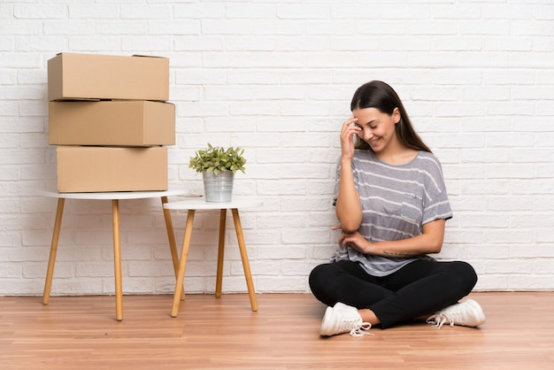 Young woman moving in new home among boxes laughing