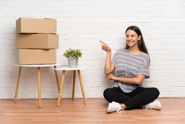 Young woman moving in new home among boxes pointing finger to the side