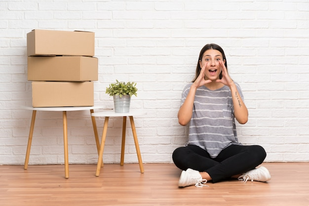 Young woman moving in new home among boxes shouting with mouth wide open