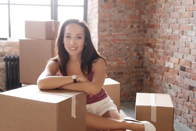 若い女性が彼女の新しいアパートに移動