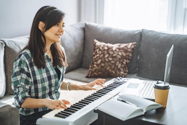 自宅で仕事をしながらラップトップを使用してリモートでエレクトリックピアノの指導をしている若い女性の音楽教師。オンライン教育とレジャーのコンセプト。
