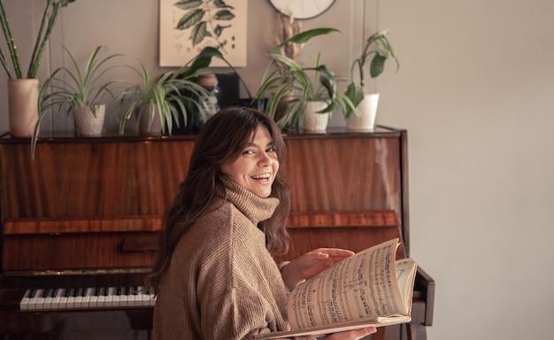若い女性ミュージシャンがピアノに座っている音符のコレクションを調べます