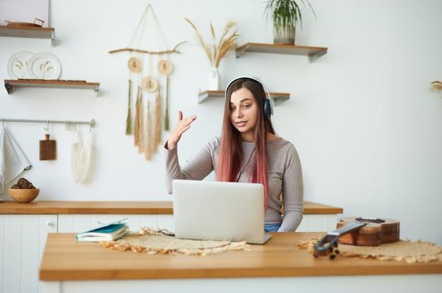 젊은 여성 음악가는 노트북을 사용하는 학생들에게 온라인 음악 수업을 가르칩니다.