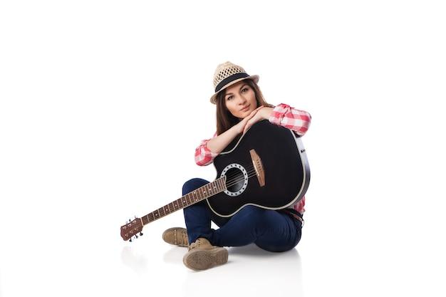 Молодая женщина-музыкант с гитарой в рубашке и шляпе, сидя на полу. белый фон.