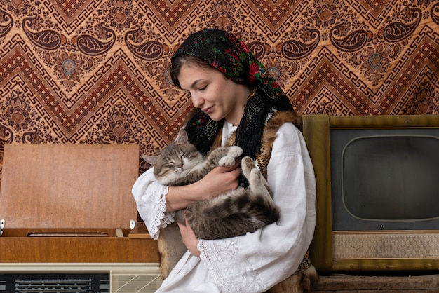 Young woman in national closes sitting among aged retro room and holding cat in her hands
