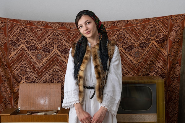 Young woman in national wjite dress and black handkerchief looking at the camera