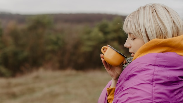 Young woman in nature drinking tea