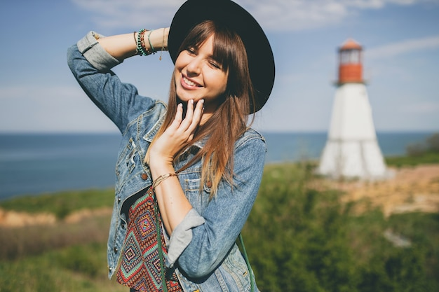 Young woman in nature, lighthouse, bohemian outfit, denim jacket, black hat, smiling, happy, summer, stylish accessories