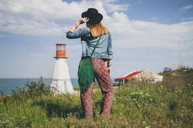 Young woman in nature, lighthouse, bohemian outfit, denim jacket, black hat, summer, stylish accessories