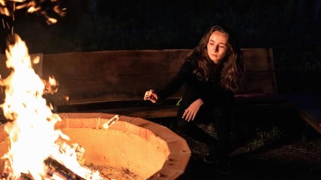 夜、グランピングでキャンプファイヤーの近くの若い女性。マシュマロの炒め物