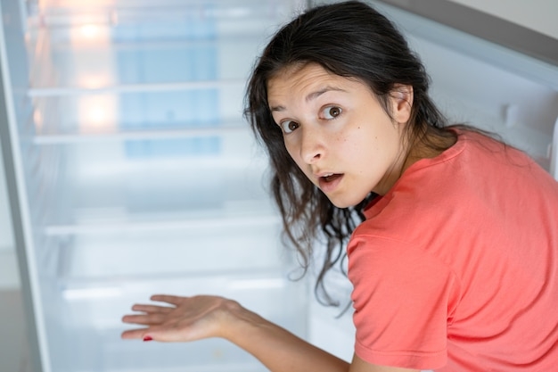 Young woman near empty refrigerator with no food