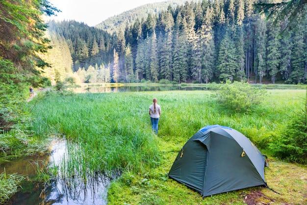 푸른 물이 있는 산속의 녹색 텐트와 숲 호수 근처의 젊은 여자