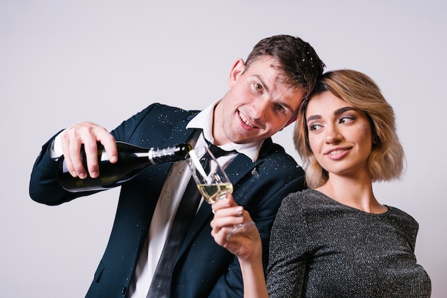 Young woman near handsome man with bottle of drink pouring glass
