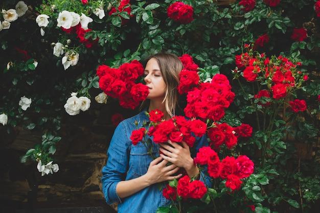 庭の赤いバラの茂みの近くの若い女性