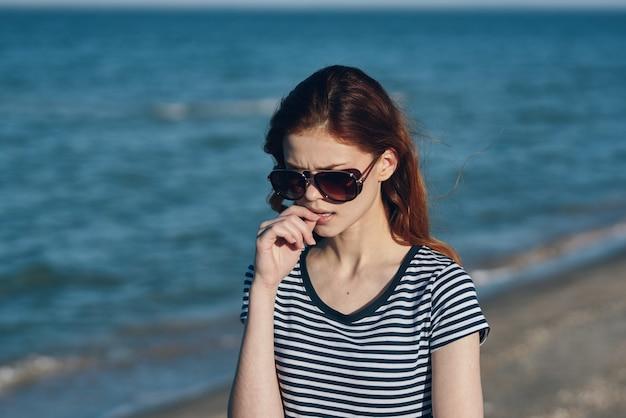 サングラスをかけた海の近くの若い女性