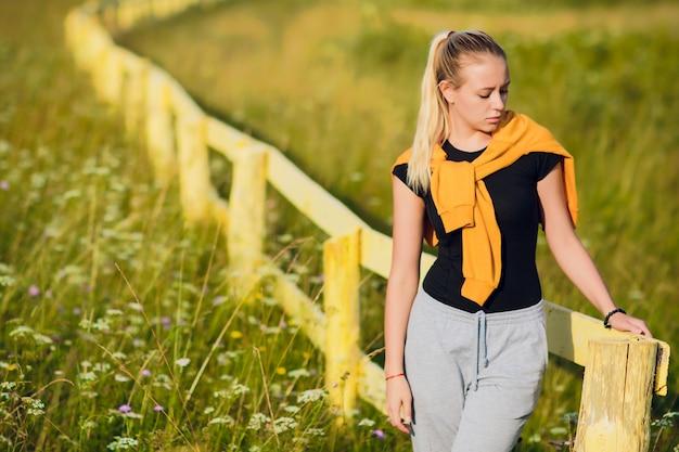 村の木の塀の近くの若い女性。