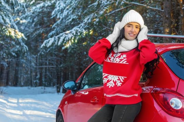冬の森の赤い車の横にある若い女性