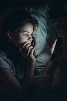 Young woman at night lies in bed with a phone in her hands