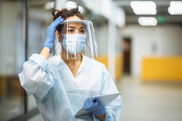 젊은 여자 간호사는 코로나 바이러스 전염병 동안 병원 복도에서 얼굴 방패를 조정합니다. 직장에서 전문 의료 노동자 초상화입니다. 의료, 의학 및 안전 개념.