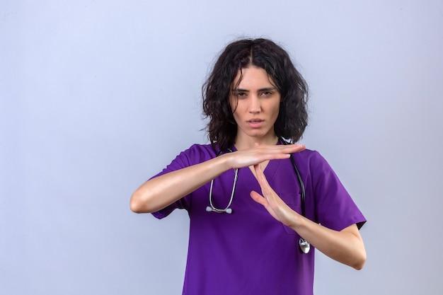 Молодая медсестра в медицинской форме со стетоскопом показывает жест тайм-аута с нахмуренным лицом