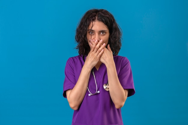 Infermiera della giovane donna in uniforme medica e con lo stetoscopio che sembra sorpreso coprendosi la bocca con le mani in piedi