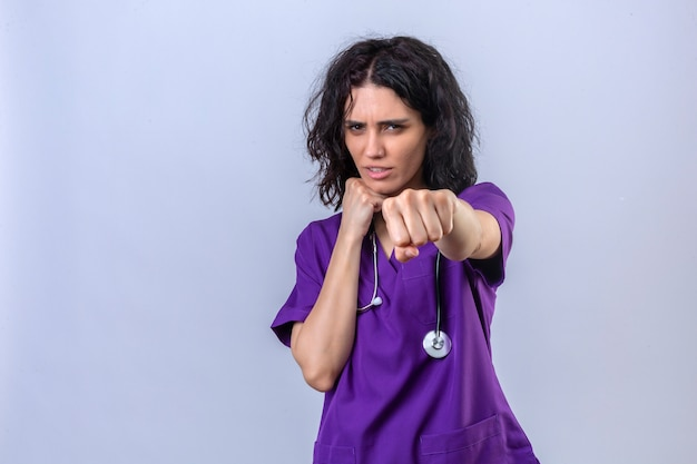 Young woman nurse in medical uniform and with stethoscope standing ready to fight with fist defense gesture angry and upset face